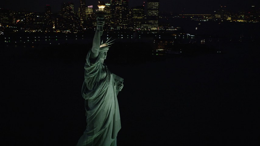 5k aerial video Flying by Statue of Liberty, revealing Lower Manhattan, New York, night Aerial Stock Footage   AX89_143