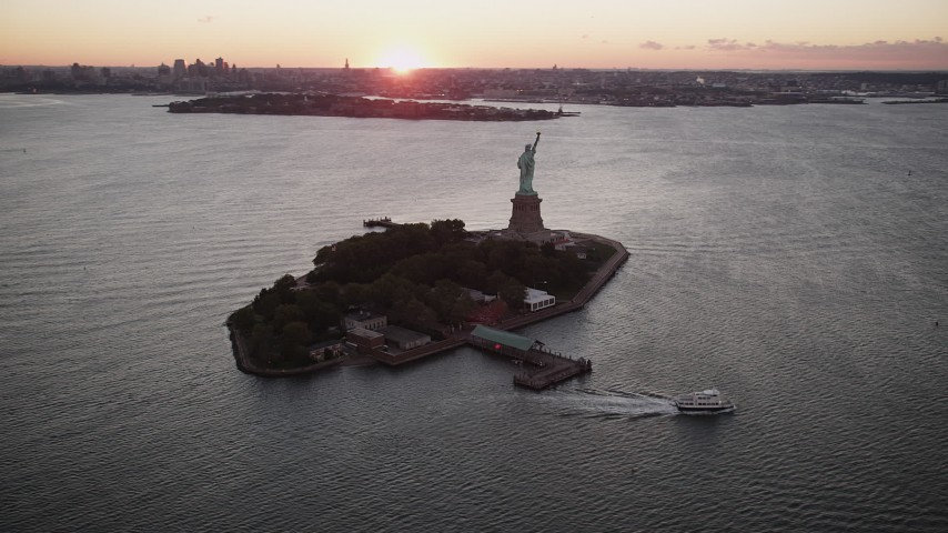 4K stock footage aerial video Flying by Statue of Liberty, Liberty Island, New York Harbor, New York, sunrise Aerial Stock Footage | AX90_001