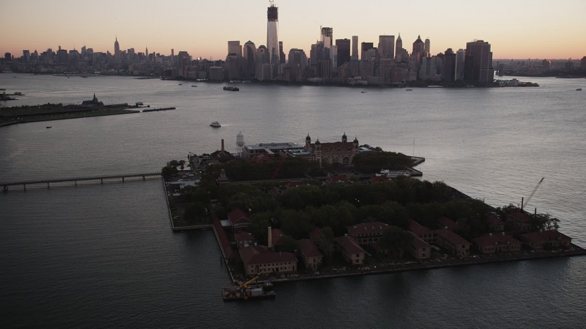 4K stock footage aerial video Approaching Lower Manhattan skyline, Ellis Island, New York, New York, sunrise Aerial Stock Footage | AX90_002