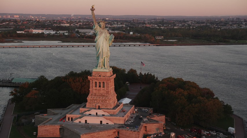 4K stock footage aerial video Flying by Statue of Liberty, Liberty Island, New York, New York, sunrise Aerial Stock Footage | AX90_015