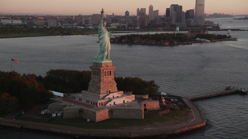 4K stock footage aerial video Flying by Statue of Liberty, revealing Lower Manhattan, New York, sunrise Aerial Stock Footage | AX90_016