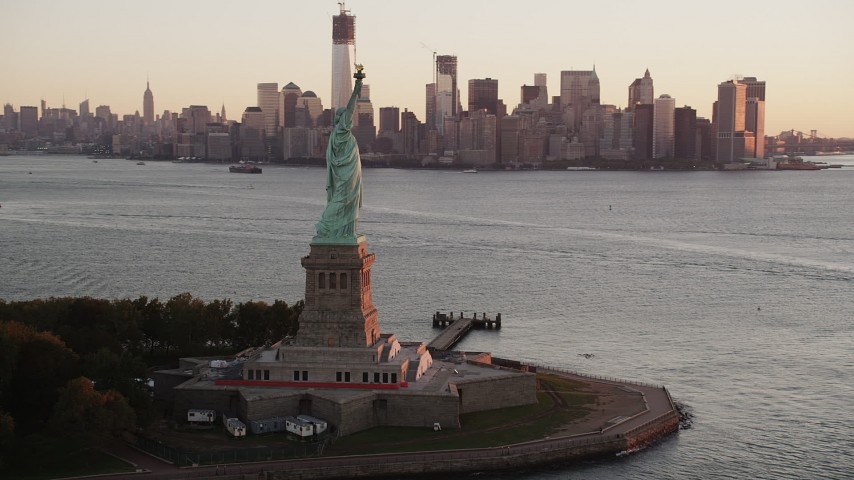 4K aerial video of the Statue of Liberty, Lower Manhattan, revealing Brooklyn, New York, sunrise Aerial Stock Footage | AX90_017
