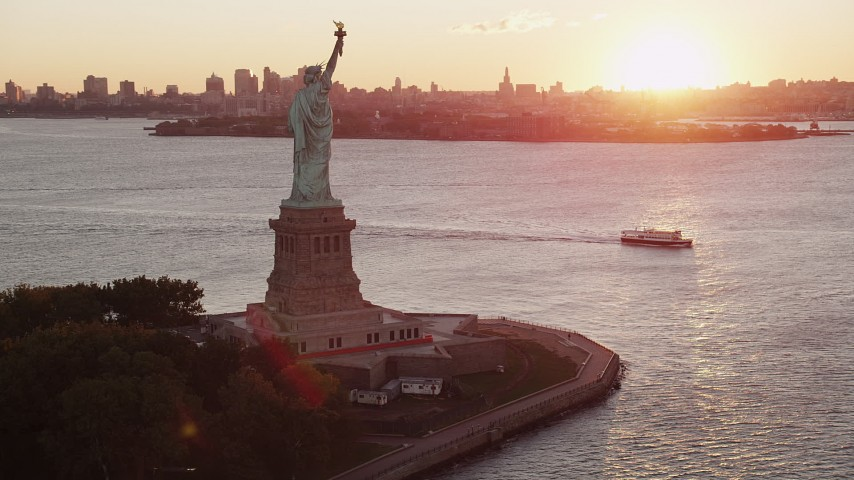 4K stock footage aerial video Flying by Statue of Liberty, Brooklyn in the distance, New York, New York, sunrise Aerial Stock Footage | AX90_018