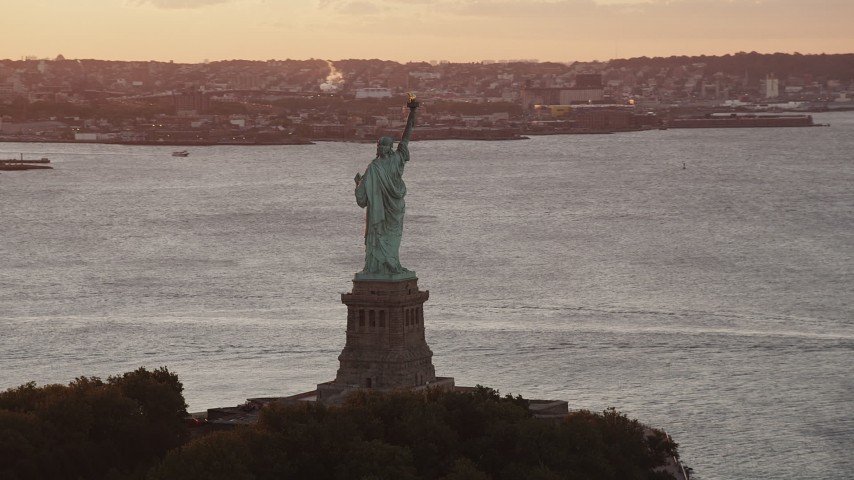 4K stock footage aerial video Flying by Statue of Liberty, Brooklyn in the distance, New York, New York, sunrise Aerial Stock Footage | AX90_019