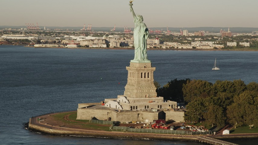 4K stock footage aerial video Flying by Statue of Liberty, Liberty Island, New York Harbor, New York, sunrise Aerial Stock Footage | AX90_139