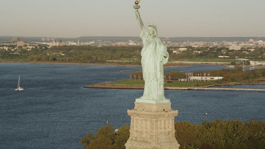 4K stock footage aerial video Flying by Statue of Liberty, Liberty Island, New York Harbor, New York, sunrise Aerial Stock Footage | AX90_140