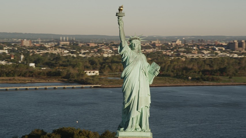 4K stock footage aerial video Flying by Statue of Liberty, Liberty Island, New York Harbor, New York, sunrise Aerial Stock Footage | AX90_141