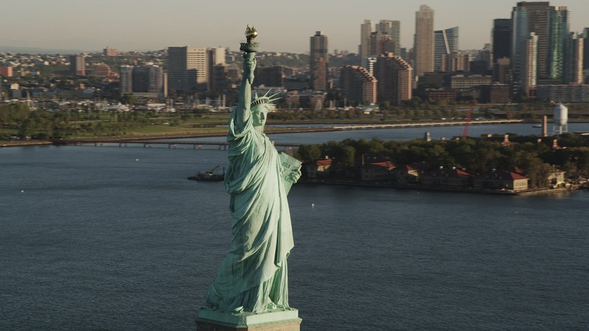 4K stock footage aerial video of Statue of Liberty, Liberty Island, reveal Midtown Manhattan, New York, sunrise Aerial Stock Footage | AX90_142