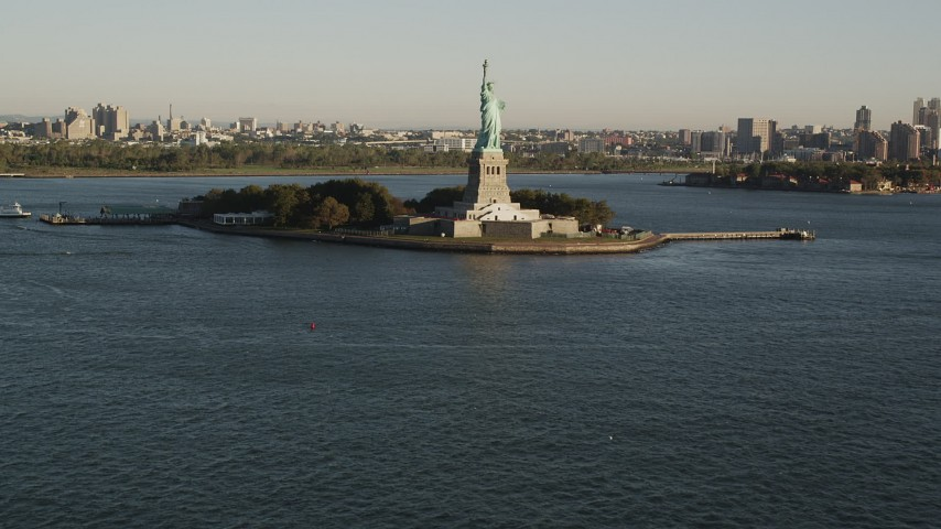 4K stock footage aerial video Tilting up from New York Harbor, revealing Statue of Liberty, New York, sunrise Aerial Stock Footage | AX90_148