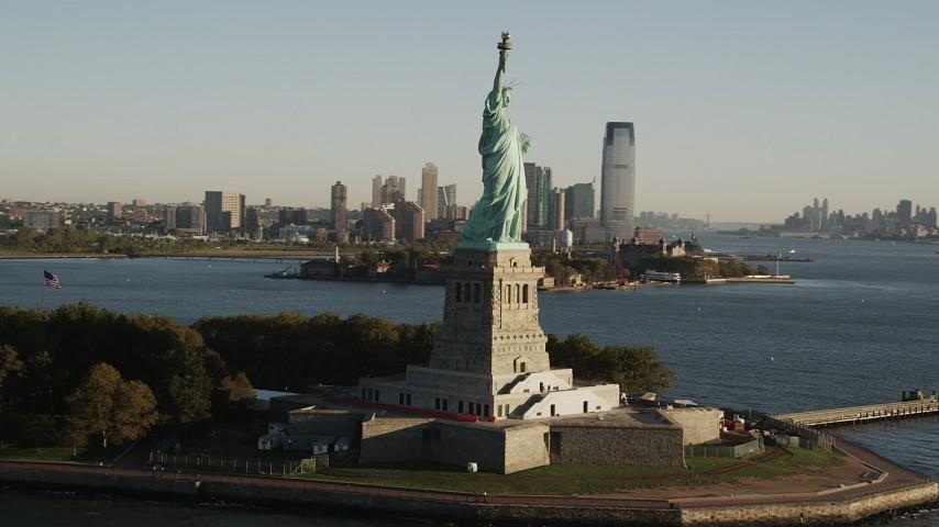 5k aerial video Orbiting Statue of Liberty, revealing Lower Manhattan skyline, New York, sunrise Aerial Stock Footage | AX90_150