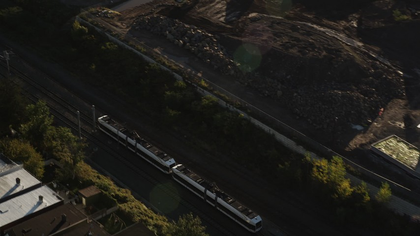 5k aerial video Tracking a commuter train, Jersey City, New Jersey, sunrise Aerial Stock Footage | AX90_162