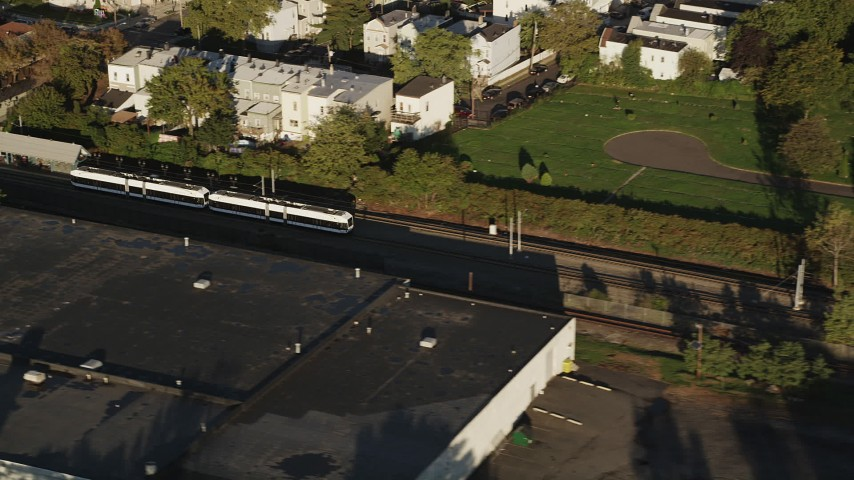 5k aerial video Tracking a commuter train passing through, Jersey City, New Jersey, sunrise Aerial Stock Footage | AX90_163