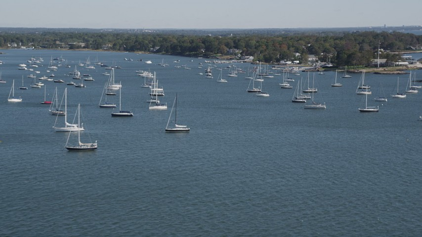 4K stock footage aerial video of tilting from the ocean to reveal sailboats near the coast, Rye, New York Aerial Stock Footage | AX91_040