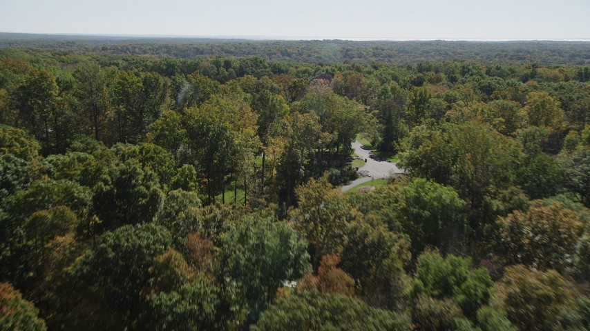 4K stock footage aerial video of flying over lush forest, revealing homes in autumn, Guilford, Connecticut Aerial Stock Footage | AX91_170