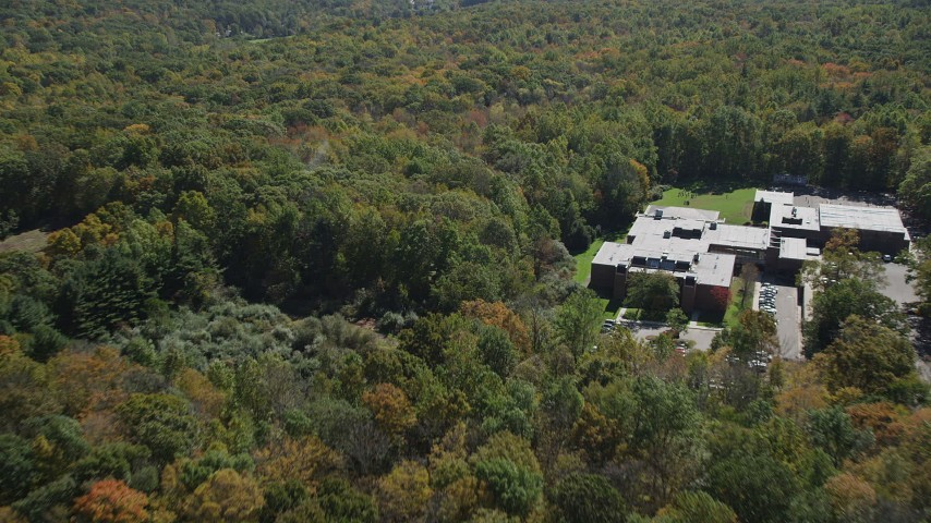 4K stock footage aerial video flyby Abraham Baldwin Middle School and over forest, autumn, Guilford, Connecticut Aerial Stock Footage | AX91_174
