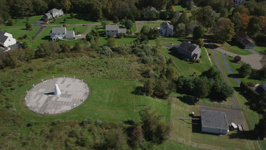 4K stock footage aerial video of flying over forest, and by sundial and houses in autumn, Guilford, Connecticut Aerial Stock Footage | AX91_180