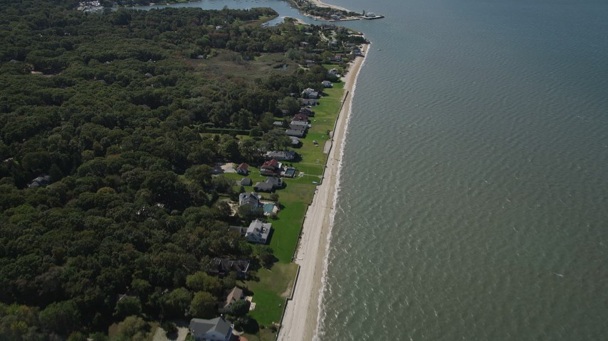 4K stock footage aerial video of flying over beachfront homes, revealing Wooley Pond, Southampton, New York Aerial Stock Footage   AX91_204