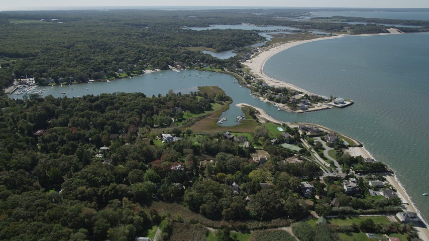4K stock footage aerial video approach Wooley Pond, tilt to upscale beachfront homes, Southampton, New York Aerial Stock Footage | AX91_205