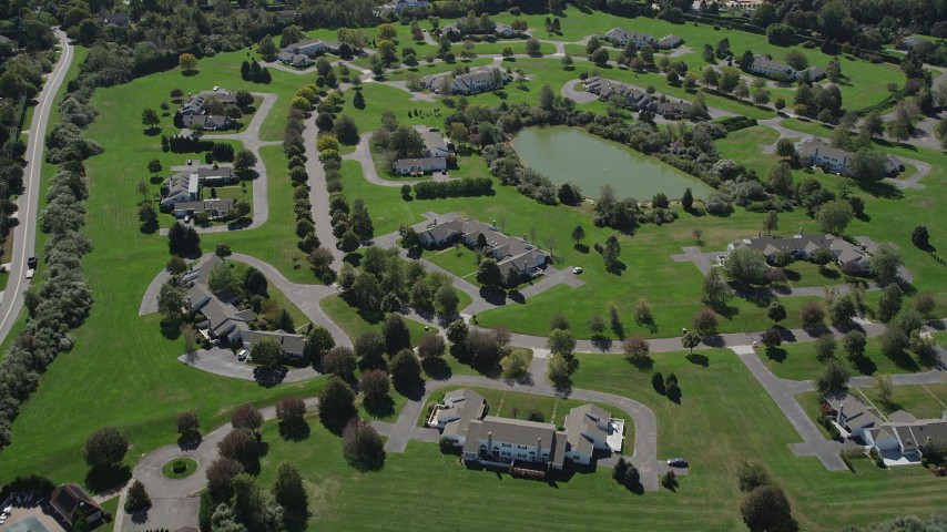 4K stock footage aerial video of flying over upscale homes near a small pond in Southampton, New York Aerial Stock Footage | AX91_209