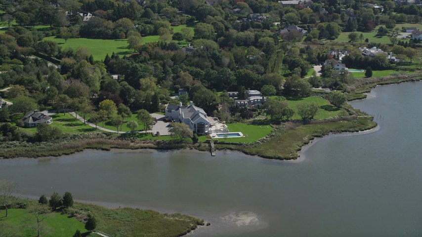 4K stock footage aerial video of flying by a waterfront mansion in Southampton, New York Aerial Stock Footage   AX91_211