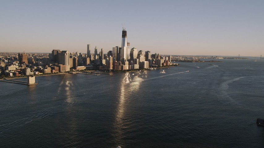 4K stock footage aerial video of Lower Manhattan skyscrapers, from Hudson River, New York, New York, sunset Aerial Stock Footage | AX93_003