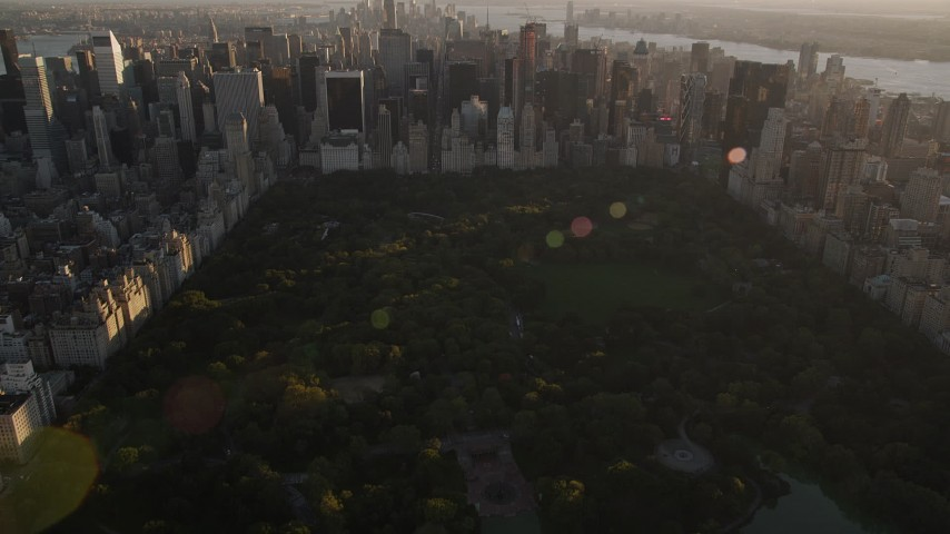 4K stock footage aerial video Flying over Central Park, tilt to Midtown Manhattan, New York, sunset Aerial Stock Footage | AX93_024
