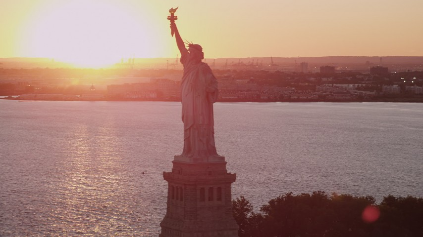 4K stock footage aerial video Flying by the Statue of Liberty, New York Harbor, New York, New York, sunset Aerial Stock Footage AX93_108 | Axiom Images