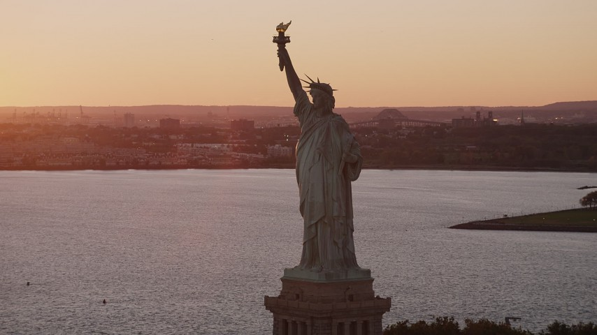 4K stock footage aerial video Flying by the Statue of Liberty, New York Harbor, New York, New York, sunset Aerial Stock Footage | AX93_109