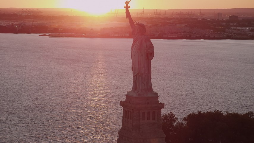 4K stock footage aerial video Flying by the Statue of Liberty, New York Harbor, New York, New York, sunset Aerial Stock Footage | AX93_112