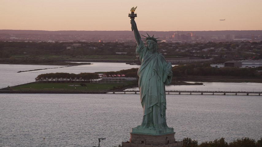 4K stock footage aerial video Flying by Statue of Liberty, New York Harbor, New York, New York, sunset Aerial Stock Footage | AX93_113