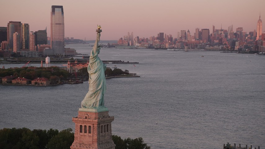 4K stock footage aerial video of the Statue of Liberty, New York Harbor, Midtown, Lower Manhattan, New York, sunset Aerial Stock Footage   AX93_115