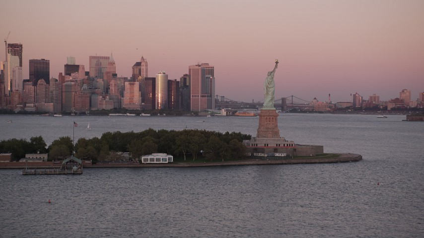 4K stock footage aerial video Approaching the Statue of Liberty, Lower Manhattan skyline, New York, sunset Aerial Stock Footage | AX93_119