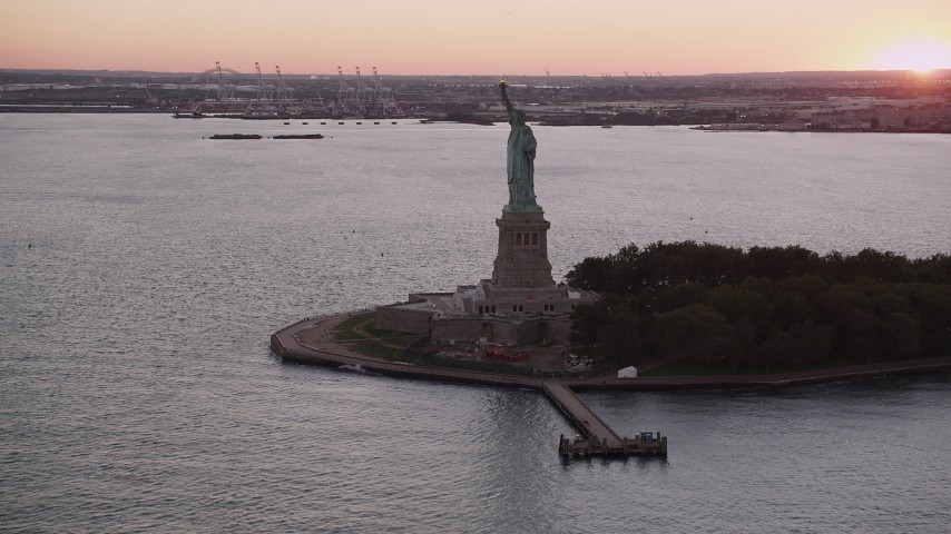 5k aerial video Flying by the Statue of Liberty, New York, New York, sunset Aerial Stock Footage | AX93_123