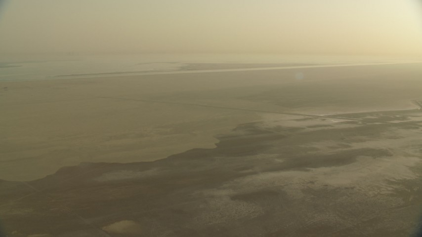 HD stock footage aerial video of flying over a hazy desert at sunrise in Al Selmiyyah, Abu Dhabi, UAE Aerial Stock Footage | CAP_001_002