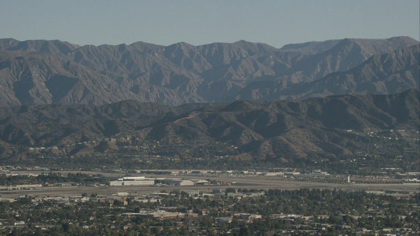 HD stock footage aerial video of Bob Hope International Airport and mountain ridges in Burbank, California Aerial Stock Footage | CAP_004_004