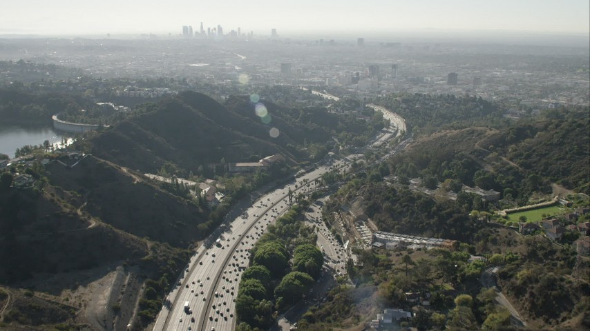 HD stock footage aerial video of tilt from freeway in Hollywood Hills to reveal Downtown Los Angeles skyline, California Aerial Stock Footage | CAP_004_008