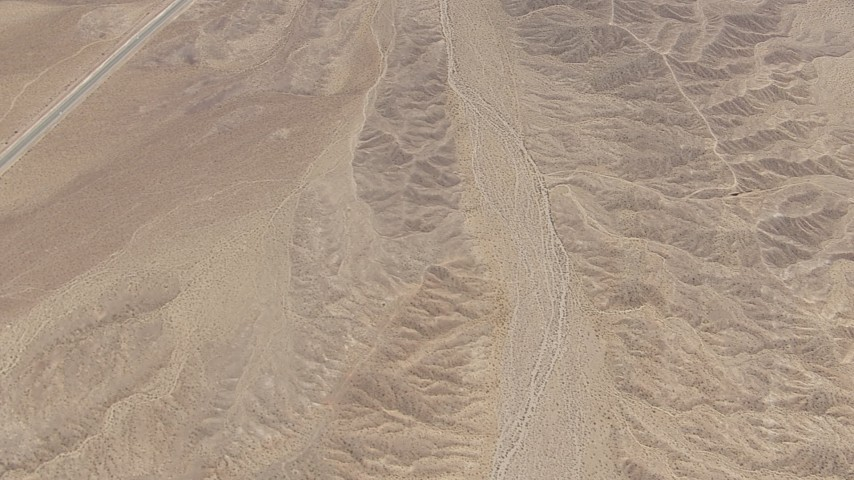 HD stock footage aerial video bird's eye view of open desert and reveal a highway in San Bernardino County, California Aerial Stock Footage | CAP_006_011