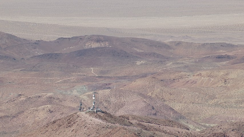 HD stock footage aerial video of a reverse view of a group of radio towers and Mojave Desert mountains in San Bernardino County, California Aerial Stock Footage | CAP_006_019
