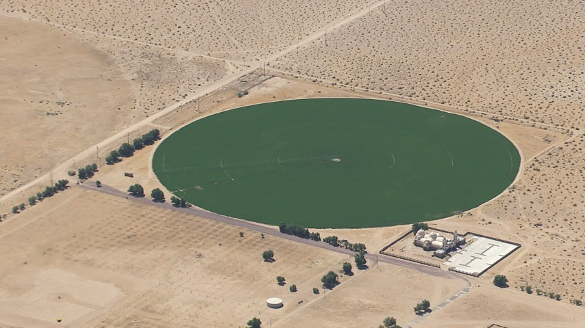 HD stock footage aerial video of a reverse view of a crop field beside a Mojave Desert monastery in Newberry Springs, California Aerial Stock Footage   CAP_006_023