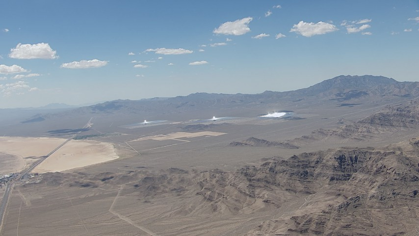 HD stock footage aerial video of a view of the three solar arrays at Ivanpah Solar Electric Generating System in California next to a highway Aerial Stock Footage | CAP_006_047