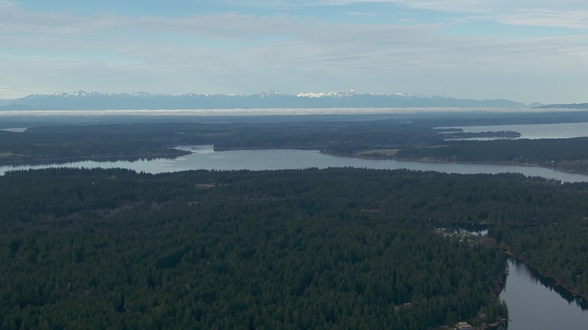 HD stock footage aerial video of a view of the Olympic Mountain range, seen from Anderson Island in Puget Sound, Washington Aerial Stock Footage | CAP_009_003