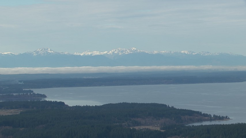 HD stock footage aerial video of the snowy Olympic Mountain range seen from Puget Sound, Washington Aerial Stock Footage | CAP_009_007