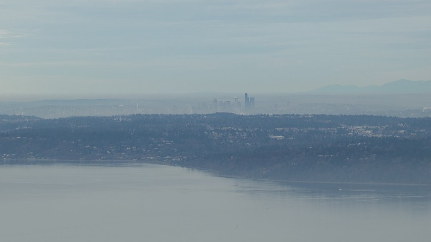 HD stock footage aerial video of the hazy Downtown Seattle skyline seen from Puget Sound, Washington Aerial Stock Footage | CAP_009_024
