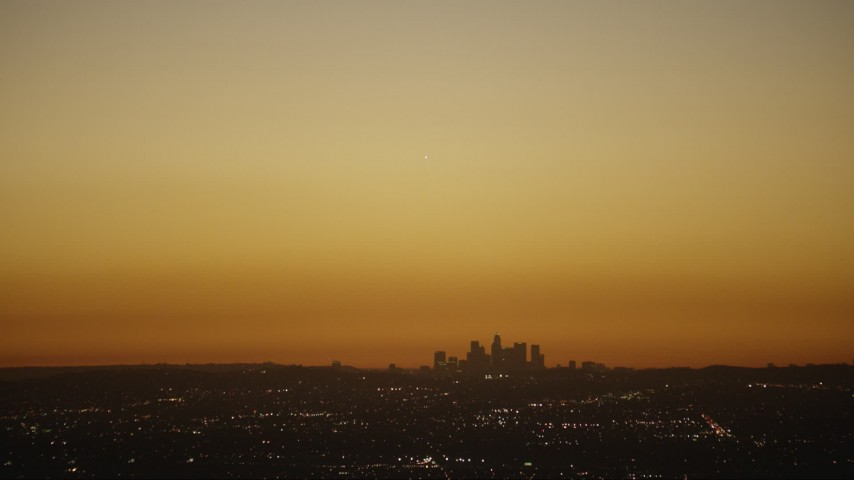 HD stock footage aerial video bright light over the Downtown Los Angeles city skyline at twilight, California Aerial Stock Footage | CAP_010_007