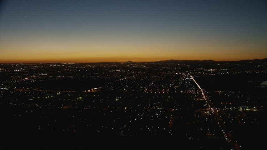 HD stock footage aerial video tilt from residential neighborhoods to reveal the Downtown Los Angeles city skyline at twilight, California Aerial Stock Footage | CAP_010_008