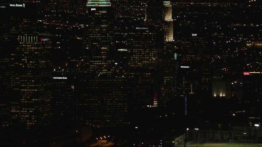 HD stock footage aerial video tilt from Downtown Los Angeles city buildings to Figueroa and Wilshire skyscraper at night, California Aerial Stock Footage | CAP_010_014