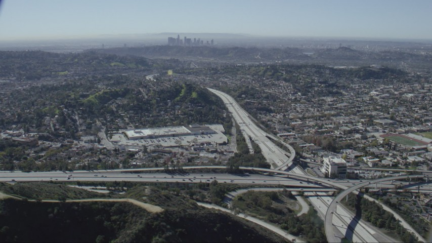 HD stock footage aerial video of the 2 and 134 freeway interchange in Glendale, California, Downtown Los Angeles skyline in background Aerial Stock Footage | CAP_012_011