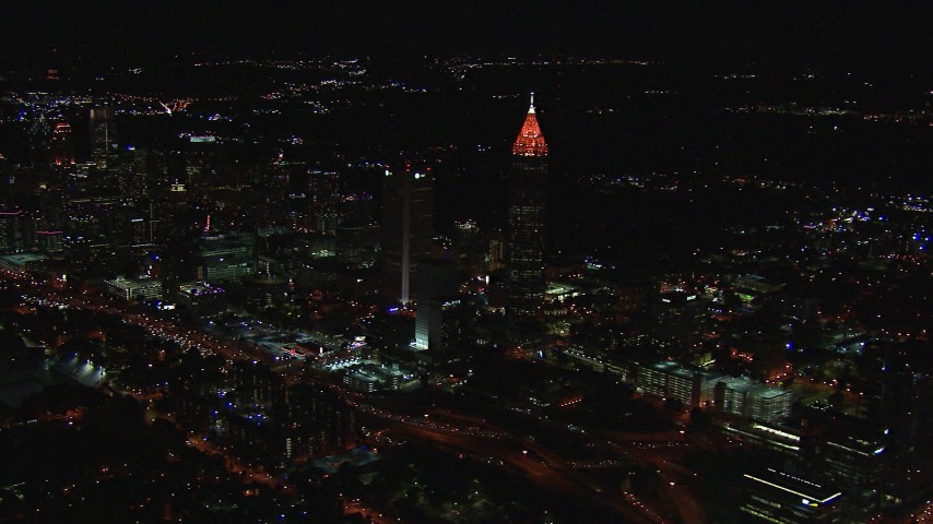 HD stock footage aerial video of flying by a tall skyscraper and city buildings at night, Midtown Atlanta, Georgia Aerial Stock Footage | CAP_013_013