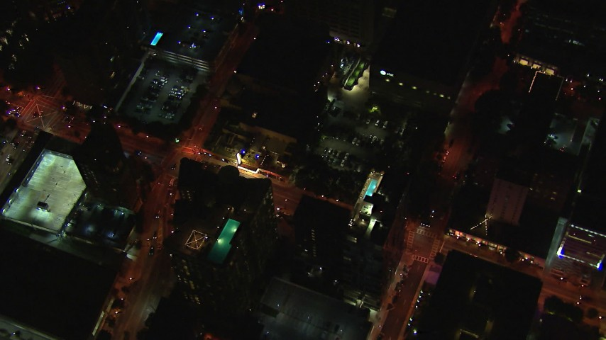 HD stock footage aerial video tilt from AT&T Center to bird's eye of rooftop hotel pool and street at night, Midtown Atlanta, Georgia Aerial Stock Footage | CAP_013_039