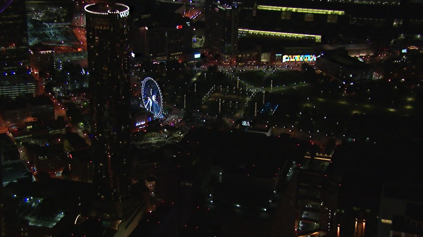 HD stock footage aerial video of a Ferris wheel at nighttime while passing skyscrapers, Downtown Atlanta, Georgia Aerial Stock Footage | CAP_013_064